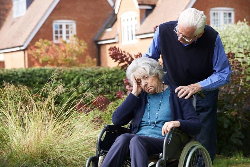 Deprimierte ältere Frau im Rollstuhl, der vom Ehemann gedrückt wird lizenzfreies stockfoto
