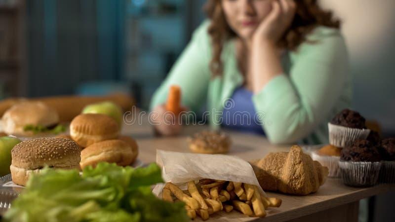 Deprimierte fette Dame, die bei Tisch voll von der ungesunden ungesunden Fertigkost, essend sitzt zu viel lizenzfreies stockbild