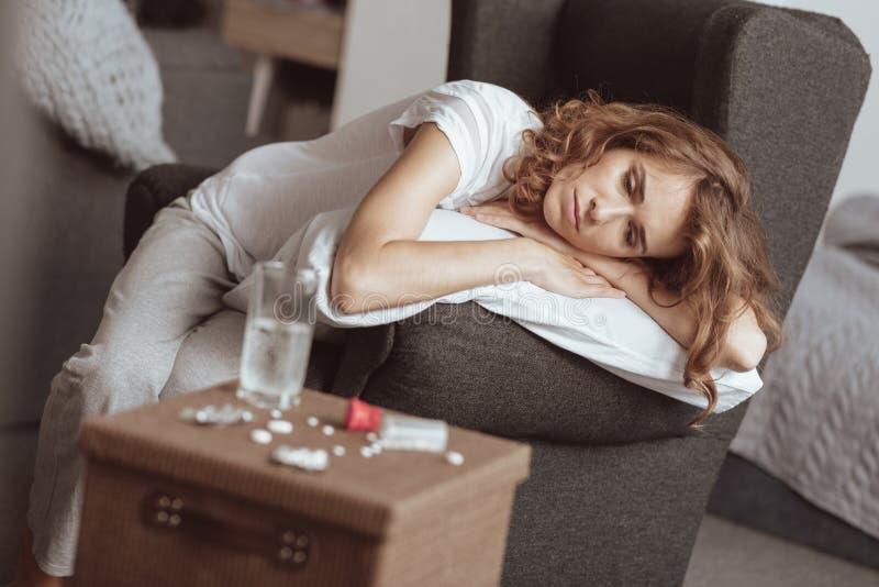Deprimierte Frau, die bei Tisch mit vielen Pillen schaut lizenzfreie stockbilder