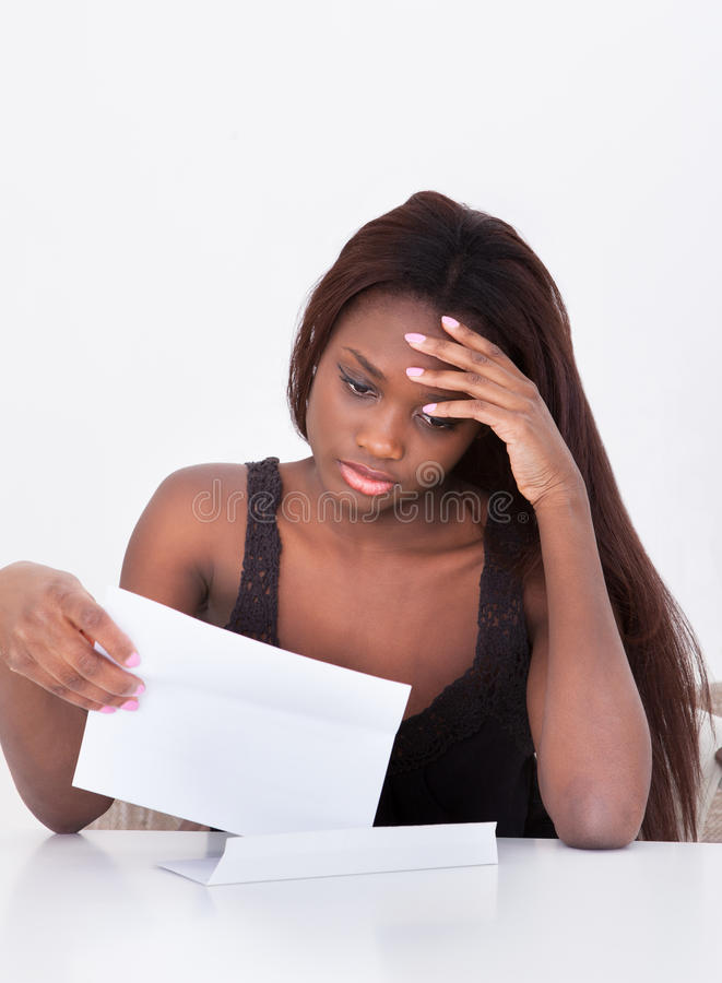 Deprimierte Frau, die Bill At Table hält stockbild