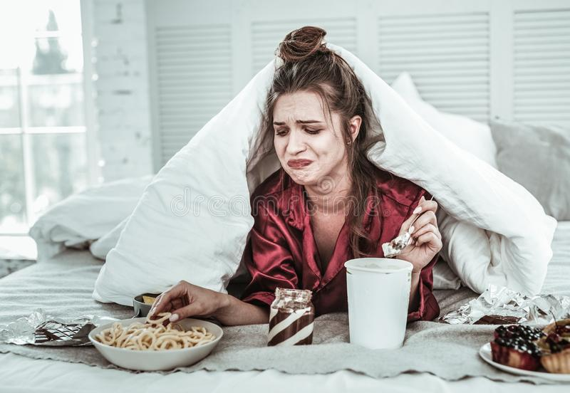 Deprimierte Frau, die Druck mit vielen von Bonbon ergreift lizenzfreie stockfotos