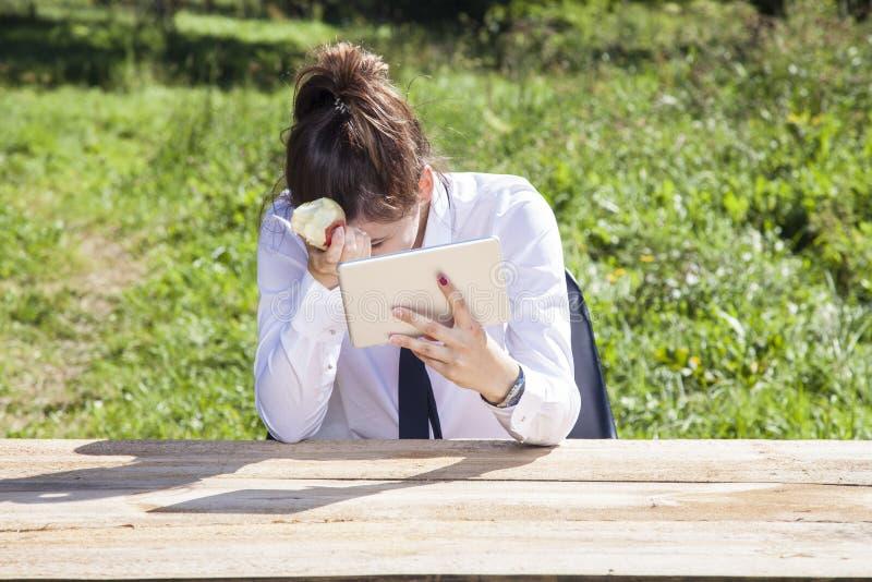Deprimierte Geschäftsfrau, die einen Apfel isst und Mitteilungen liest lizenzfreie stockbilder