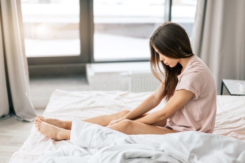 Deprimierte junge aufgebrachte Frau, die im Bett sitzt lizenzfreie stockfotografie
