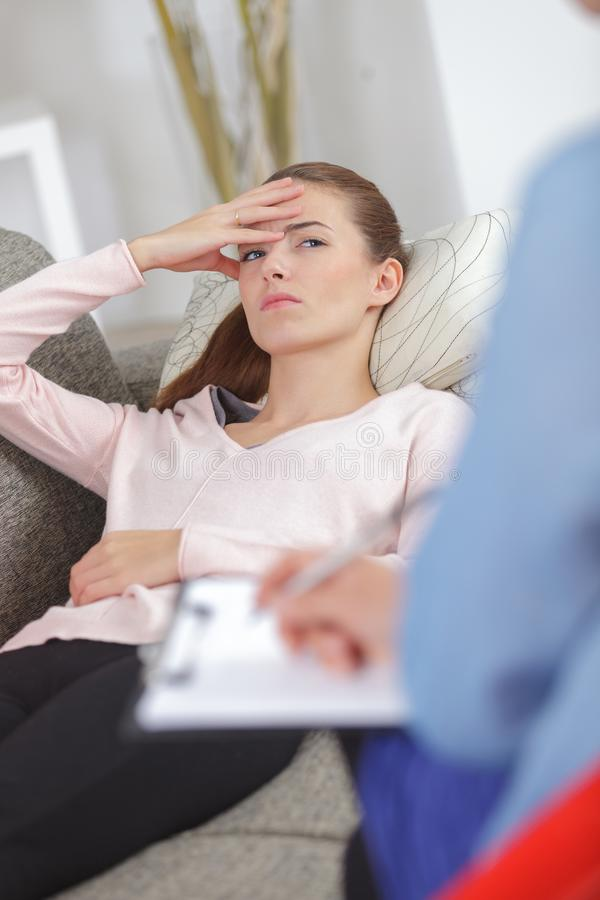 Deprimierte junge Frau, die auf Couch am Psychotherapeuten liegt stockbilder