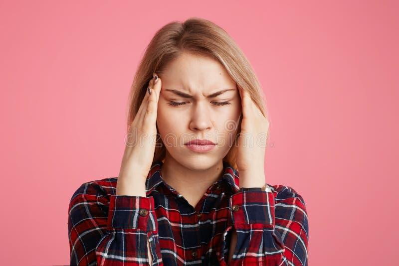 Deprimierte stressige Frau hat Kopfschmerzen, hält Hände auf Tempeln, schließt Augen als schreckliche Schmerz des Fühlunges und i stockbilder