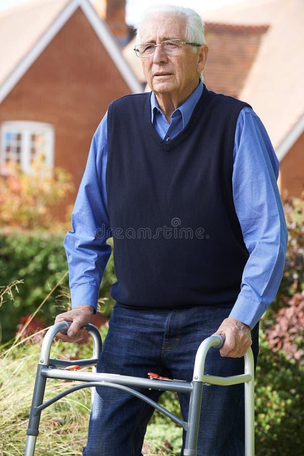 Deprimierter älterer Mann, der draußen gehenden Rahmen verwendet lizenzfreie stockfotos