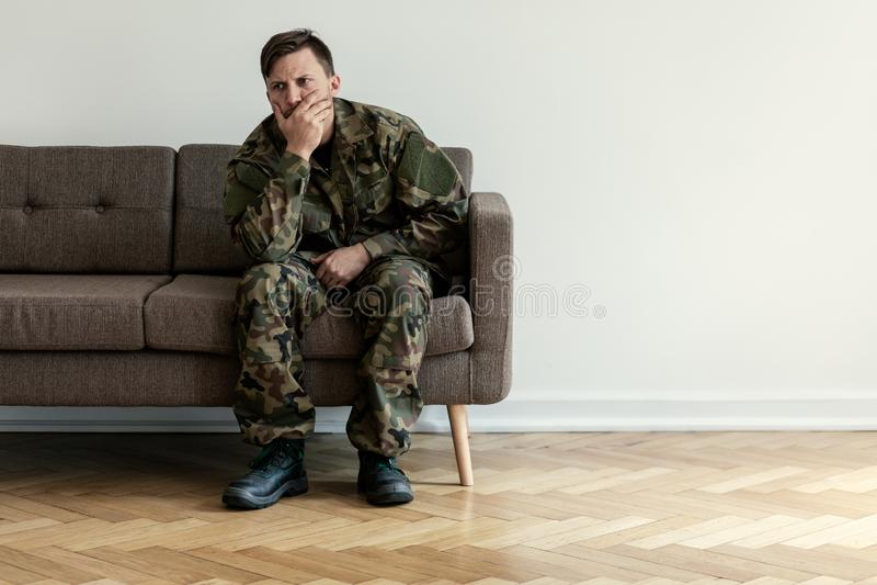 Deprimierter Berufssoldat in der grünen Uniform, die allein zu Hause sitzt Kopieren Sie Raum auf der Wand lizenzfreie stockfotos