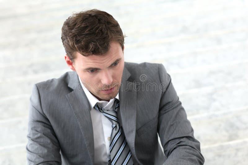 Deprimierter Geschäftsmann, der draußen sitzt lizenzfreie stockfotografie