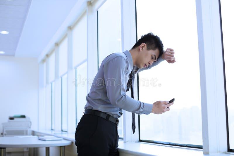 Deprimierter junger Geschäftsmann, der intelligentes Telefon schaut stockfotos