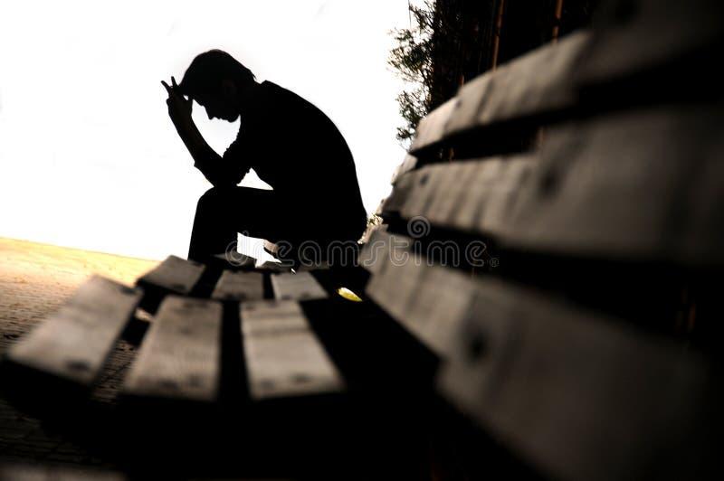 Deprimierter junger Mann, der auf der Bank sitzt stockfotos