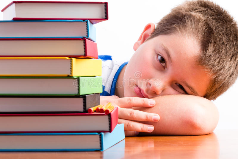 Deprimierter junger Schüler, der seine Lehrbücher mustert lizenzfreies stockfoto