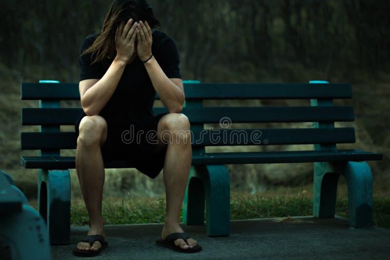 Deprimierter Mann, der auf einer Parkbank bedeckt sein Gesicht mit seinen H?nden sitzt lizenzfreie stockbilder