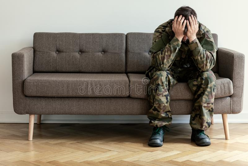 Deprimierter Soldat in der grünen Uniform mit Kriegssyndrom auf dem Sofa, das für Therapeuten wainting ist stockbilder