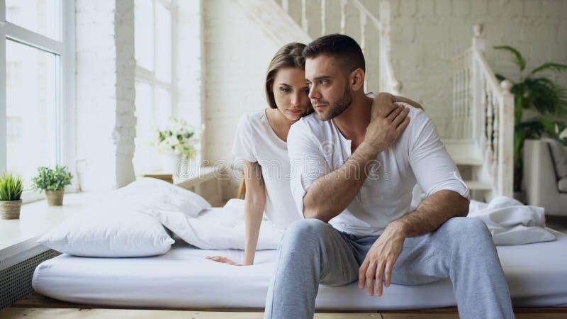 Deprimierter Yong-Mann, der im betonenden Bett sitzt, während seine Freundin kommen ihn umfassen und küssen im Schlafzimmer zu Ha stockfotografie