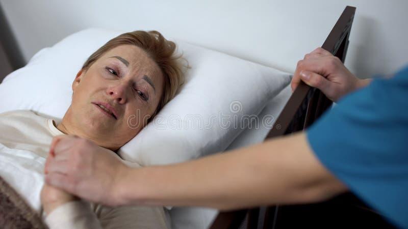 Deprimiertes älteres Patientenschreien, liegend im Krankenbett, freiwillige Unterstützungsdame stockfotos