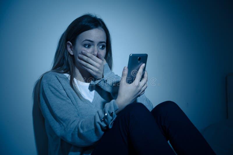 Deprimiertes Jugendlichmädchen auf dem Handyopfer des cyberbullying Gefühls traurig, unglücklich und einsam lizenzfreies stockfoto