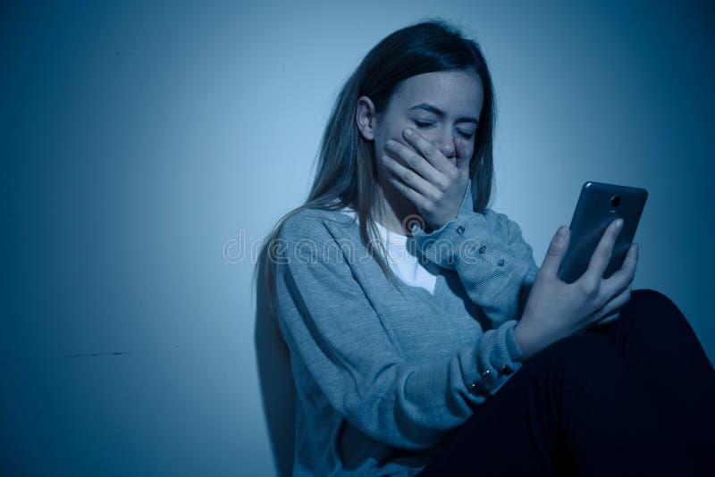 Deprimiertes Jugendlichmädchen auf dem Handyopfer des cyberbullying Gefühls traurig, unglücklich und einsam lizenzfreie stockfotografie