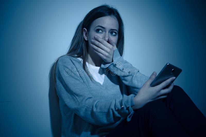Deprimiertes Jugendlichmädchen auf dem Handyopfer des cyberbullying Gefühls traurig, unglücklich und einsam lizenzfreies stockbild