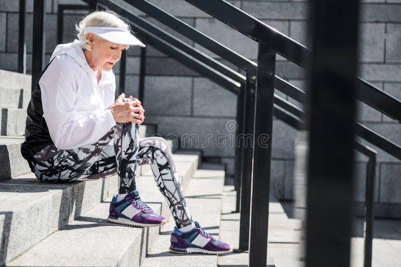 Deprymujący starzejącej się kobiety ma odpoczynek na kamiennej stadium drabinie fotografia stock