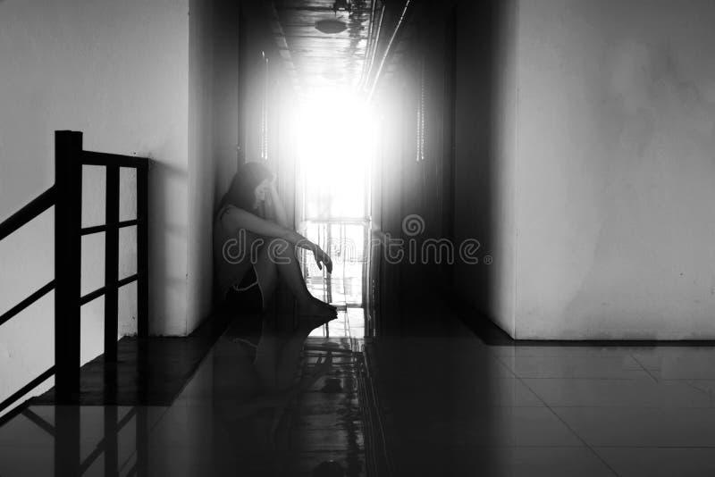 Deprymuje przy corrido i beznadziejny kobiety obsiadanie w zmroku zdjęcie stock