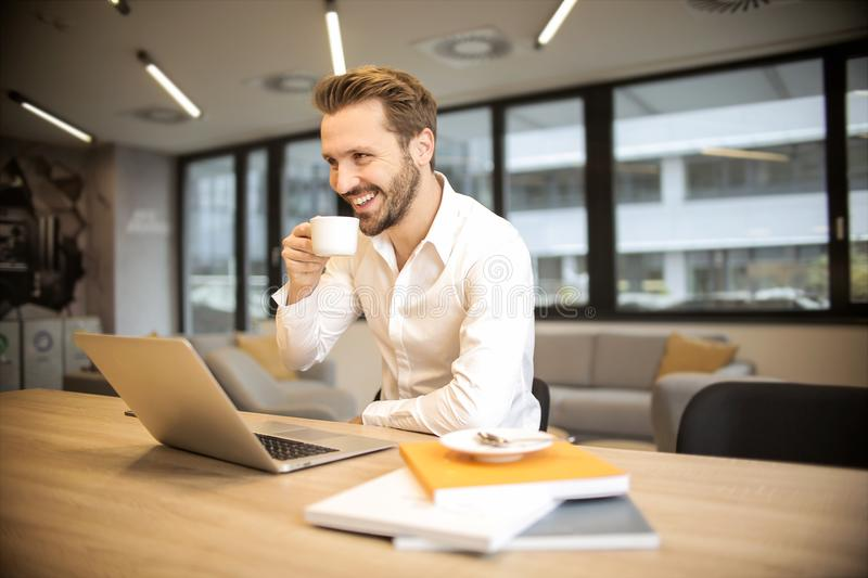 Depth of Field Photo of Man Sitting on Chair While Holding Cup in Front of Table stock image