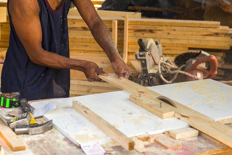 Der ältere männliche Tischler, der Tabelle verwendet, sah für den Schnitt des Holzes am worksh stockbilder