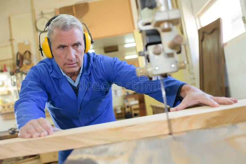 Der ältere männliche Tischler, der Tabelle verwendet, sah für den Schnitt des Holzes stockfoto