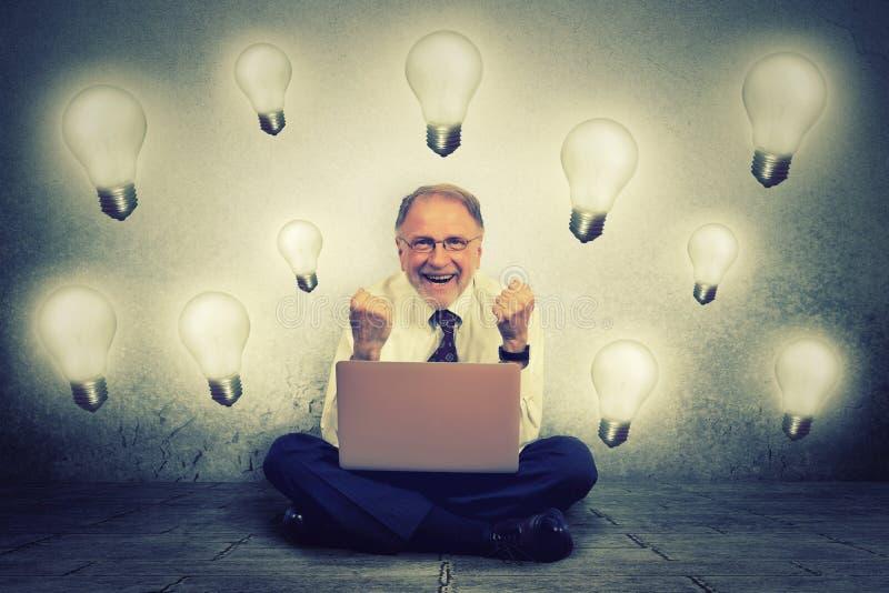 Der ältere Mann, der an Computer arbeitet, den, Glühlampe herein ihn verstopfte, feiert Geschäftserfolg stockbilder