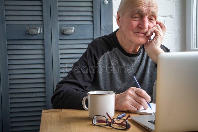 Der ältere Mann, der an Laptop, Zählung, Schirm betrachtend, trinkender Tee arbeitet und macht Anmerkungen in einem Notizbuch stockbilder