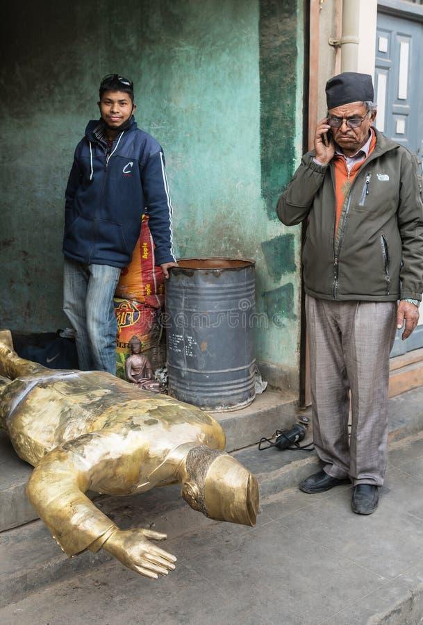 Der ältere Nepalese neben seinem die Bronzeskulptur lizenzfreie stockfotografie