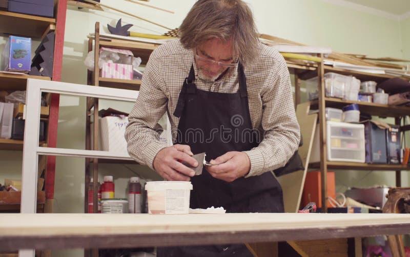 Der ältere Tischler, der ein hölzernes Brett spackling ist lizenzfreie stockfotografie