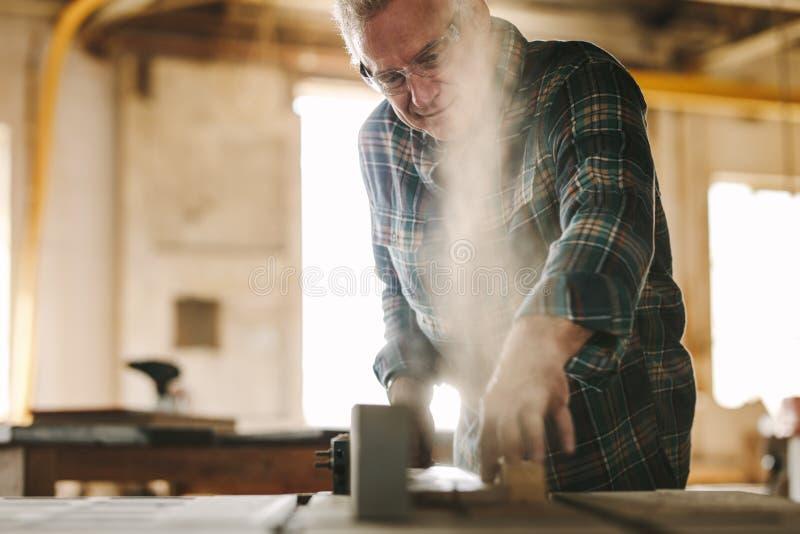 Der ältere Tischler, der Holz auf Tabelle schneidet, sah Maschine stockfoto