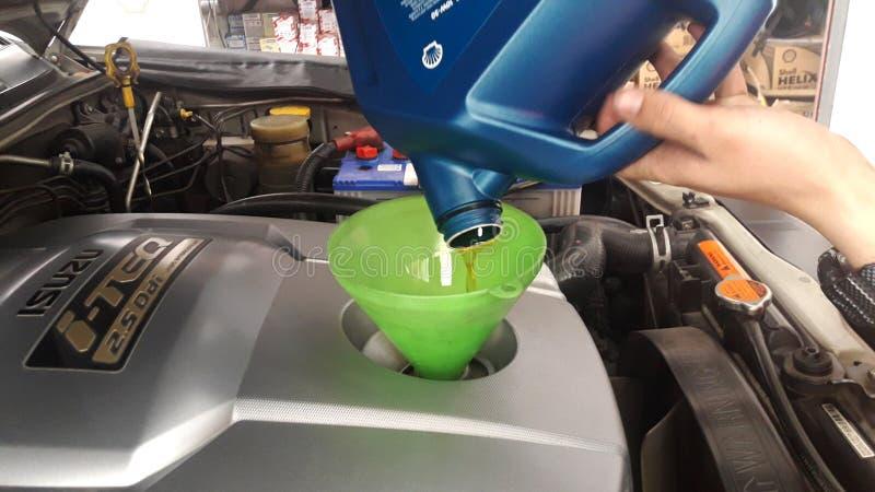 Der Ölwechsel, der genommen aus der Maschine heraus abgelaufen wird, bereiten sich für neues Motoröl vor stockfotografie