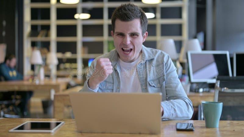 Der überraschend junge Designer feiert Erfolg auf Laptop im Büro stockfotos