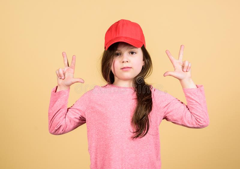 Der Abnutzungs-Kappe des M?dchens netter Kinderbeige Hintergrund oder des Hysteresenhutes Wenig M?dchen, das helle Baseballm?tze  stockbilder