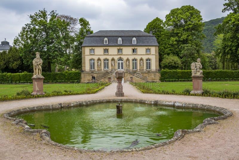 Der Abteigarten in Echternach, Luxemburg mit einem Brunnen und dem Gebäude der Orangerie an einem bewölkten Maifeiertag stockbild