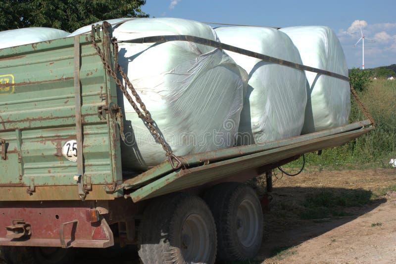 Der Ackerwagen, der mit sechs Heusilageballen eingewickelt wurden mit Enzym geladen wurde, goss Folie hinein lizenzfreie stockbilder