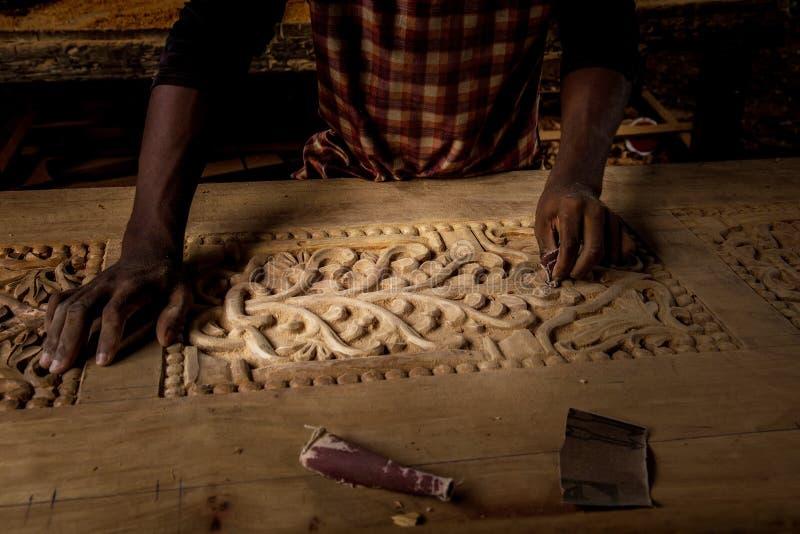 Der afrikanische Mann, der seine Arbeit erledigt, macht eine Transchiermessertür lizenzfreie stockfotografie