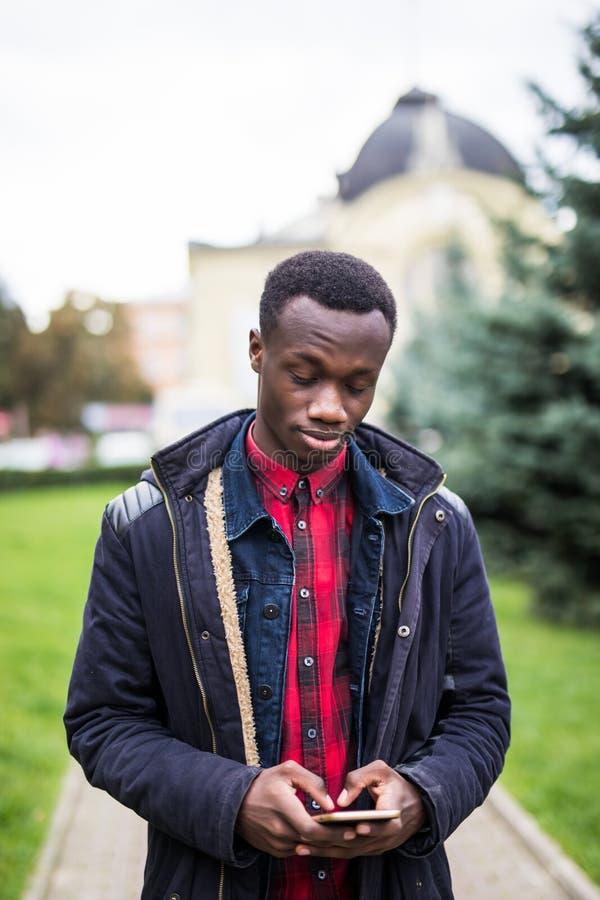 Der Afroamerikaner, der intelligentes Telefon in der beschäftigten Stadt verwendet, um zu bleiben, schloss mit Social Media an de stockbild