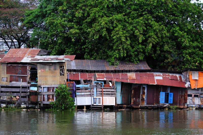 Der alte Flussufer degradieren Haus von gew?lbter Blechtafel unter gro?em Baum lizenzfreies stockfoto