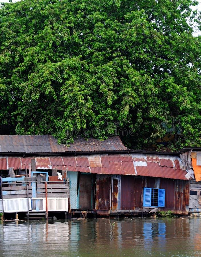 Der alte Flussufer degradieren Haus von gew?lbter Blechtafel unter gro?em Baum stockfoto