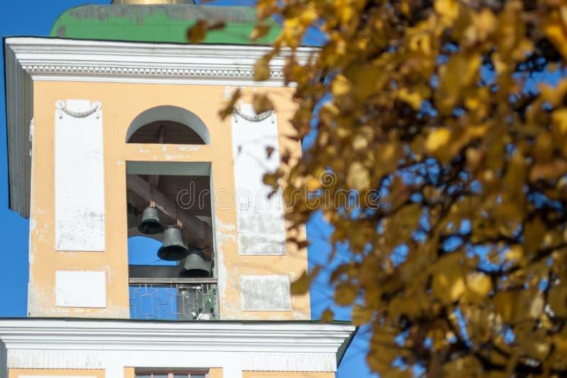 Der alte Glockenturm mit Glocken und gelbem Herbstlaub lizenzfreie stockfotografie