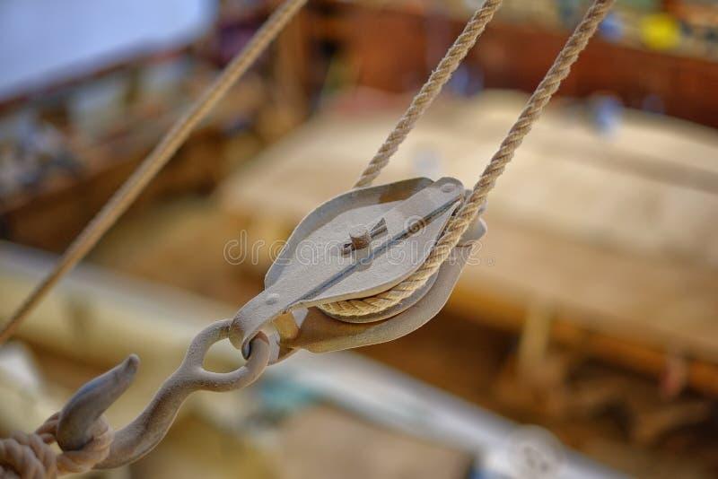 Der alte hölzerne Flaschenzug, der in den Erbauern eines Bootes hängt, kaufen stockbilder