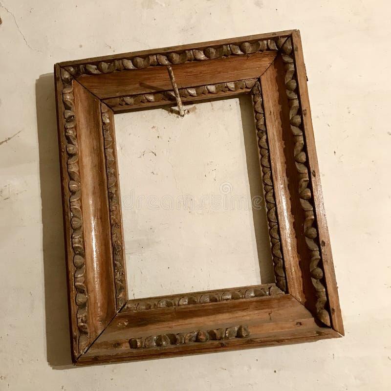 Der alte hölzerne leere Fotorahmen, der an der Wand hängt, nagelte rostigen Stahlnagel stockfoto