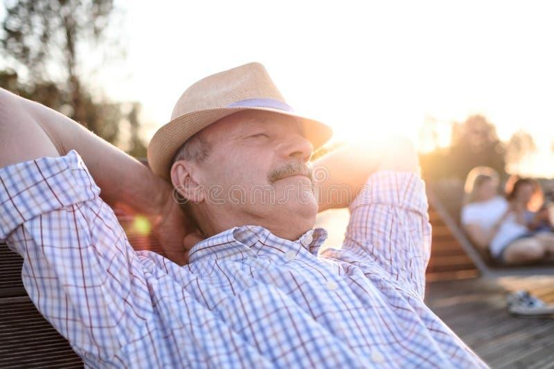 Der alte hispanische Mann sitzt auf Bank und lächelt und genießt sonnigen Tag des Sommers lizenzfreie stockfotos