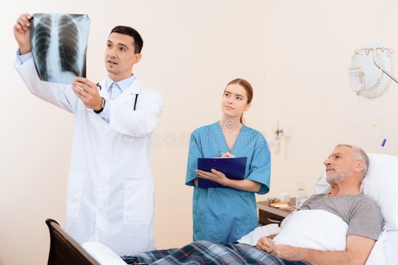 Der alte Mann liegt auf einem Feldbett im medizinischen Bezirk Nahe bei ihm ist ein Doktor und eine Krankenschwester stockfotografie