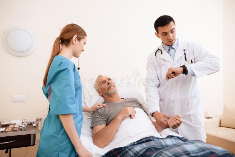 Der alte Mann liegt auf einem Feldbett im medizinischen Bezirk Nahe bei ihm ist ein Doktor und eine Krankenschwester stockfoto