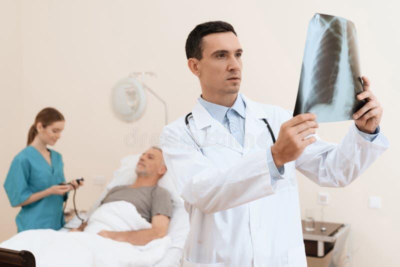 Der alte Mann liegt auf einem Feldbett im medizinischen Bezirk, und nahe bei ihm gibt es einen Doktor und eine Krankenschwester lizenzfreie stockfotografie