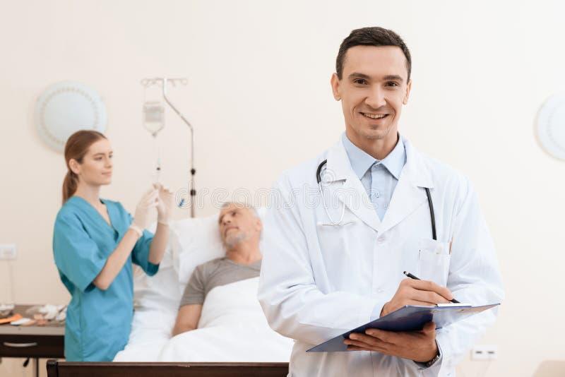 Der alte Mann liegt auf einem Feldbett im medizinischen Bezirk, und nahe bei ihm gibt es einen Doktor und eine Krankenschwester stockbild