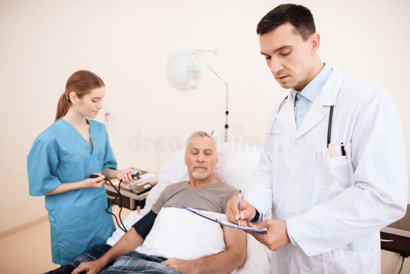 Der alte Mann liegt auf einem Feldbett im medizinischen Bezirk, und nahe bei ihm gibt es einen Doktor und eine Krankenschwester stockfotos